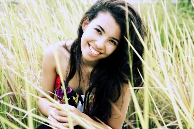 Juliet Devette sitting in tall grass