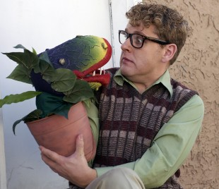 "Publicity photo for The Grand Theatre's rendition of ""Little Shop of Horrors"" featuring Trevor Dean as Seymour Krelborn and the puppet of Audrey II"