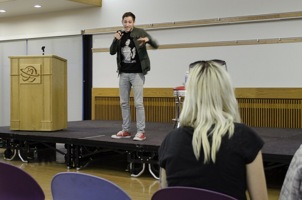 Comedian Samuel Comroe performs on a stage as a student sits in the foreground.