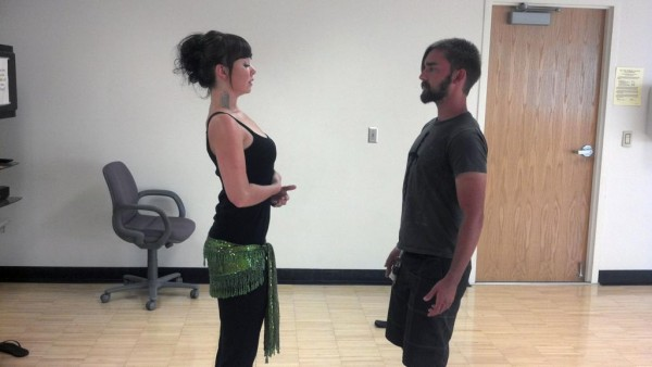 Belly dance instructor Annie McIntire teaches student Bruce Daw the correct belly dance posture.