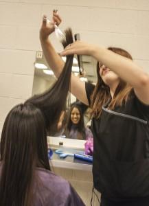 Miltzi Hernandez recieves a haircut from Brooke Ajer