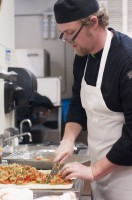 Culinary student is chopping food in the prep area of the Utah State Capitol cafeteria.