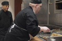 Culinary student Justin Lane is preparing hashbrowns at the grill in the Utah State Capitol cafeteria.