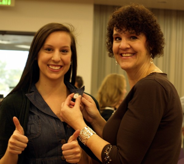 Dean's List Honoree Kierstin Johnson smiles proudly as her mother fastens her awarded pin