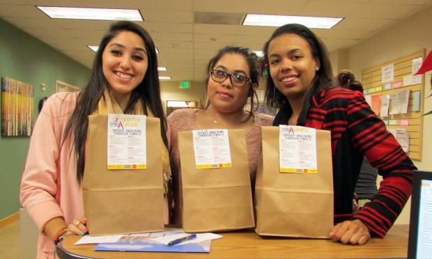Three students with Food for A Grade snack bags