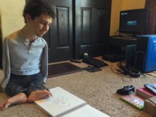 Gideon DiMeglio drawing on a sketch pad using his feet