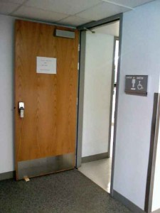 Meadowbrook Campus' men's restroom door propped open during class hours for full accessibility, a temporary solution that sparked complaints from students and staff.