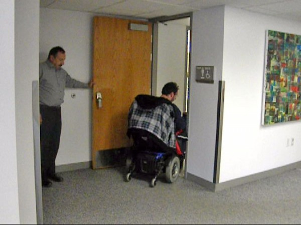Russ Collett assists Anthony Nelson enter the restroom at Meadowbrook Campus. Facilities Services is currently searching for a solution to have the door electronically activated.