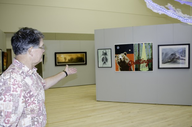 Gordon Storrs shows off the paintings entered into the President's Art Show