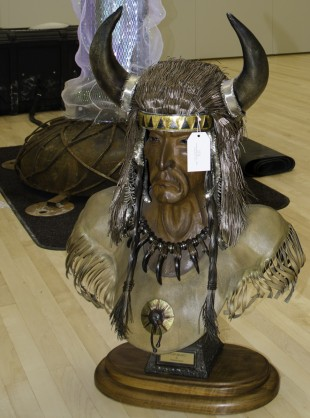 A sculpture of a Native-American wearing a buffalo headdress.