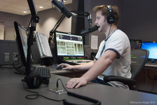 Student Michael Waters sits at the microphone as he does his radio show live