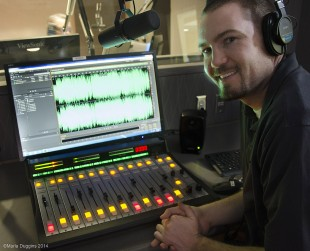 Station Manager Zac Hodge sits at the control board as he monitors a radio broadcast