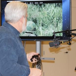 Jon Clark rubs audio tape to simulate the sound of grass