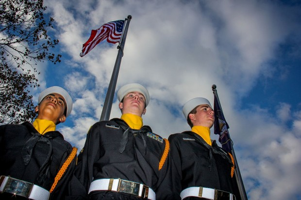 Navy officers stand in front of American flag