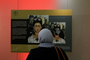 An exhibit goer views one of Kahlo's many self portraits.