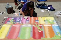 Catlin Blackmore puts the finishing touches on her colorful sidewalk art