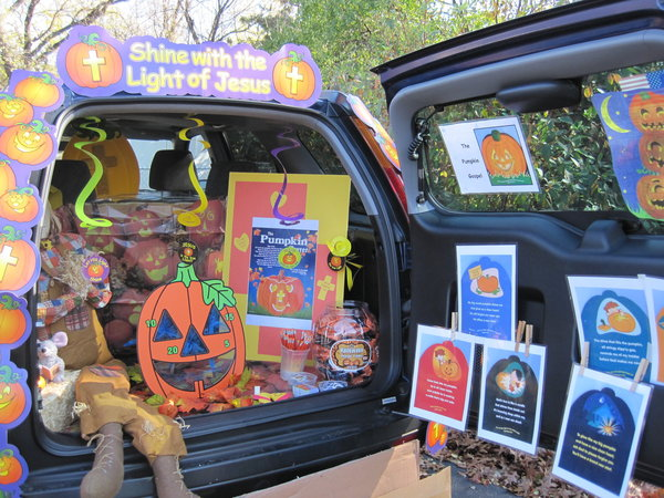 A car's trunk decorated with Halloween decorations, with a bean bag toss game being the feature attraction.