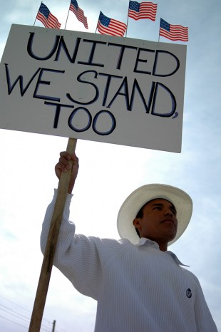 "Protester holds a ""United we stand too"" sign"