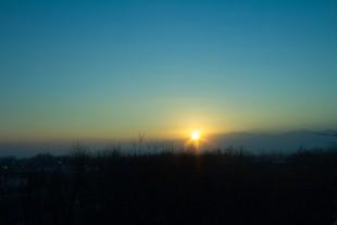 Sunrise filtered by inversion haze