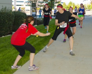 A zombie attempts to steal a flag off the belt of one of the runners.