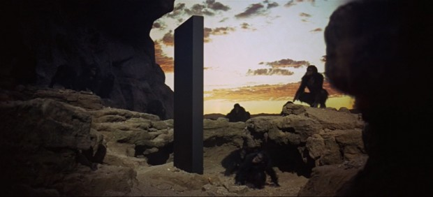 A still from 2001: A Space Odyssey featuring the apes surrounding the monolith