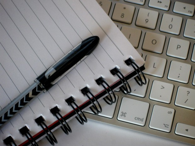 A pen resting atop a notebook that is laying on top of a laptop keyboard